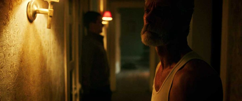 Don't Breathe's Dylan Minnette and Stephen Lang in the hallway.